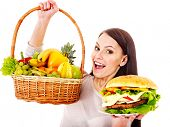 Thinking woman choosing between fruit and hamburger.