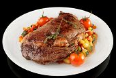 Tasty ribeye steak with stir fried vegetables isolated on black background