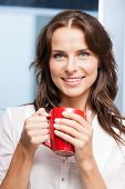 indoor picture of smiling woman with red cup