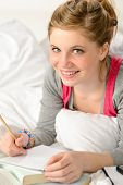 Smiling girl preparing for exams with books lying on bed