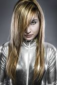Serious young blond, concept future and modernity, girl in silver latex