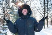 Smiling Man Wearing Fur Hooded Parka Coat In The Winter Park