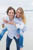 Portrait of a young man piggybacking beautiful woman at the beach