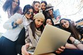 Happy teen girls having good fun time outdoors using laptop
