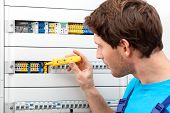 pic of fuse-box  - Repairman checking a voltage and fixing a switchboard - JPG