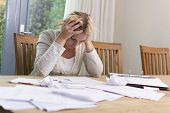 stock photo of responsibility  - Woman at table stressed about unpaid bills - JPG