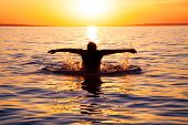 young man swims in the sea over sunrise