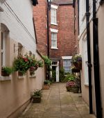 Narrow Alley Leading To Red Brick House