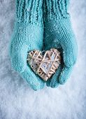 Female hands in light teal knitted mittens with entwined beige flaxen heart  on a white snow backgro