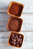 cocoa beans, powder and grated chocolate in wooden bowls, white wood backdrop