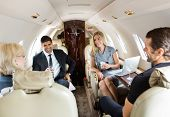 Confident business professionals having drinks on a private jet