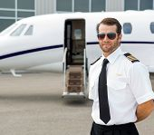 Portrait of confident pilot wearing sunglasses with private jet in background
