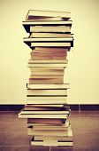 stock photo of bookworm  - picture of a pile of books on the floor with a retro effect - JPG