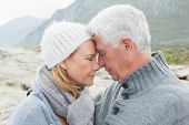 Close-up side view of a romantic senior couple together on a rocky landscape