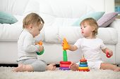 Two barefoot kids sit on carpet and play with pyramids near sofa. Focus on left kid. Shallow depth o