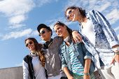 summer holidays and teenage concept - group of smiling teenagers in sunglasses hanging outside