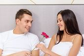 hotel, travel, relationships, holidays and happiness concept - smiling couple in bed with pink flowe