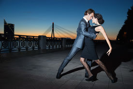 foto of boys night out  - young couple dancing tango on the quay of the river city Riga night - JPG