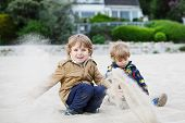 Two Little Sibling Boys Sitting On Beach Of River Elbe And Playing Together With Sand