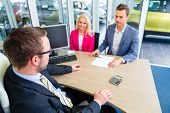 stock photo of negotiating  - Couple buying car at dealership and negotiating price with salesman - JPG