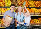 Family against shelves of fruits goes shopping. Father keeps a bag with fruits and vegetables, son h