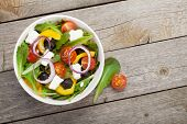 Fresh healty salad on wooden table. View from above with copy space