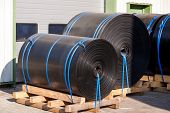 picture of wooden pallet  - Rolls of black industrial plastic tied to wooden pallets outside a warehouse or factory for use as waterproofing in building and construction - JPG