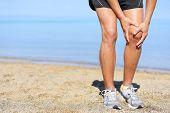 Running injury - Man jogging with knee pain. Close-up view of runner injured jogging on the beach cl