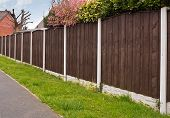 stock photo of wooden fence  - Close board fence erected around a garden for privacy with wooden fencing panels concrete posts and kickboards for added durability - JPG