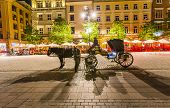 Coachman Waits For Tourists By Night With Horse-drawn Carriage At The Market Square