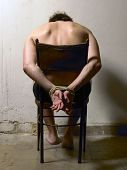 stock photo of torture  - Tortured man on a chair with tied hands. Vertical
