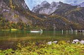 Cloudy day in the Bavarian lake Koenigssee. White tourist pleasure boat floats on the lake