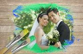 Composite image of newlyweds smiling at camera with paintbrush dipped in green against wooden surfac