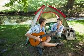 pic of serenade  - Cute man serenading his girlfriend on camping trip on a sunny day - JPG
