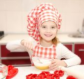 Smiling Little Girl With Chef Hat Stirrring Cookie Dough