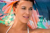 stock photo of vivacious  - Beautiful vivacious young woman wearing a bikini and holding a colorful scarf around her shoulders enjoying a hot summer day at the seaside giving the camera a lovely friendly smile ocean background - JPG