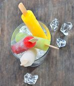 fruit ice pops on old wood background