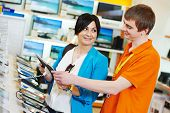 stock photo of supermarket  - Young woman choosing tablet pc computer set with shop assistant in home appliance shopping mall supermarket - JPG