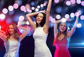 new year, celebration, friends, bachelorette party, birthday concept - three beautiful women in evening dresses dancing in the club