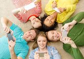 education, technology and happiness concept - group of young smiling people lying down on floor in c