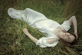 Dreamy girl lying in grass.Hommage to Pre-Raphaelities painters.