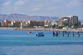 AQABA, JORDAN - MARCH 14, 2014: People on the pier against new hotels of North beach. The city has o