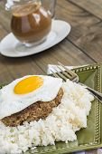 image of loco  - Loco Moco a traditional Hawaiian dish of teriyaka flavored ground beef patty and a fried egg on a bed of rice smothered in gravy