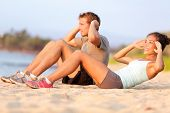 Situps training - young mixed race couple on beach sand in sunset happy smiling working out doing fi