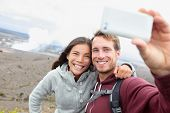 Hawaii - couple sefile by Hawaiian volcano. Travel tourists happy taking self-portrait with smart phone by Halemaumau crater within the Kilauea Volcano caldera inside hawaii volcanoes national park
