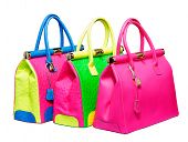 Three bright neon pink, blue and green bags with gold lock and ostrich texture leather isolated on w