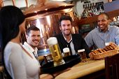 Happy young men sitting at table in pub in pub looking at waitress holding beer, smiling.