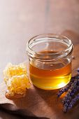 honeycomb and honey in jar on wooden background