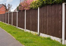 stock photo of joinery  - Close board fence erected around a garden for privacy with wooden fencing panels concrete posts and kickboards for added durability - JPG