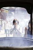 TOKYO, JAPAN - CIRCA MAY 2014: Tourists pray at Senso-ji Temple in Tokyo,Japan. The Senso-ji Temple is the symbol of Asakusa and one of the most famed temples in Japan.